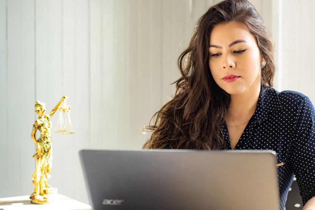Advogada a utilizar um computador com pequena estátua de justiça cega