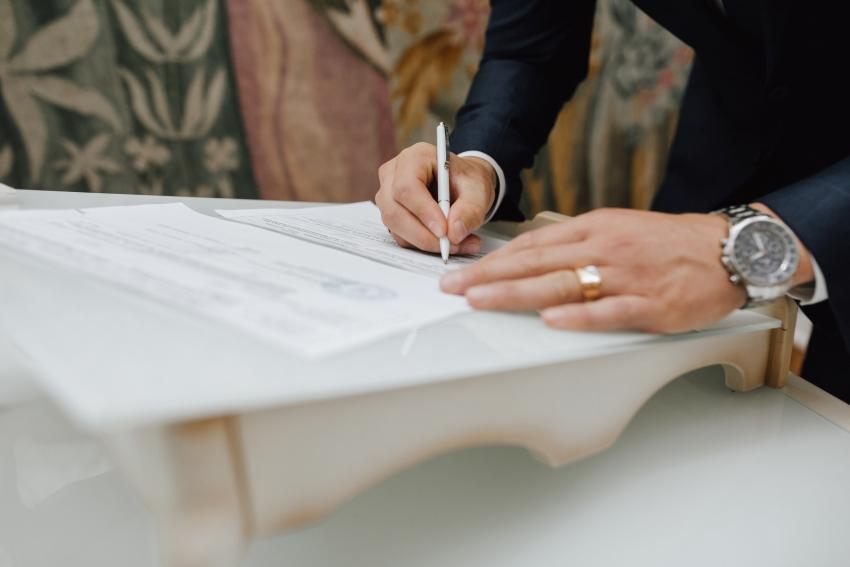 Noivo a assinar registo de casamento