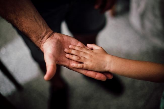 Mão de criança em cima da palma da mão de uma adulto.