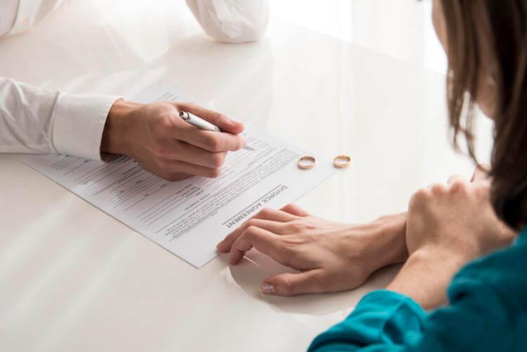 Casal a assinar documentos de divórcio.
